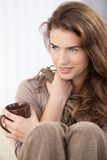 Young woman sitting with pulled up legs smiling Royalty Free Stock Photos