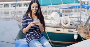 Young woman sitting on a quay checking her mobile. Young woman sitting on a quay at a marine harbour checking her mobile for messages with boats moored behind Stock Images