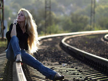 Young woman sitting on rail Stock Photos