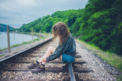 Young woman sitting on railroad tracks Royalty Free Stock Photography