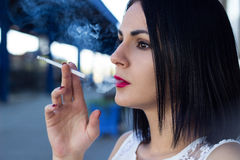 Young woman sitting on a railway station and smokes a cigar Stock Photo