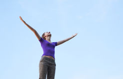 Young woman sitting with raised hand. Young woman staying with raised hands against blue sky Stock Photo