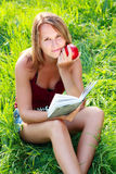 Young woman sitting reading book an apple in hand Stock Images