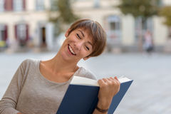 Young woman sitting reading a book outdoors royalty free stock photo
