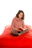 Young woman sitting and reading a book on red square shaped bean royalty free stock photography