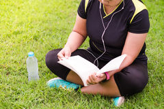 Young woman sitting and reading book something on green grass be. Side her have plastic bottle putting it stock image