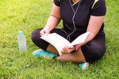 Young woman sitting and reading book something on green grass be. Side her have plastic bottle putting it royalty free stock photos
