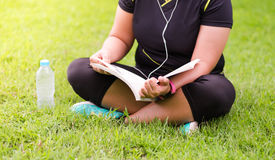 Young woman sitting and reading book something on green grass be Stock Photography