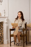 Young woman sitting reading a long document. Stylish attractive young woman sitting reading a long document in a retro wooden armchair alongside a marble Stock Photos