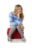 Young Woman Sitting on a  Red Suitcase Stock Images