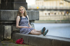Young  woman sitting relaxed on the promenade. Royalty Free Stock Photo
