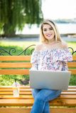Young woman sitting and relaxing on the Park Bench and using laptop. Stock Photo