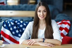 Young woman sitting in the restaurant. American flag behin stock image