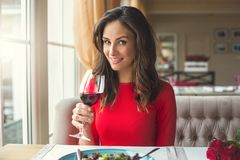 Young woman sitting in the restaurant dining drinking wine looking camera stock photography