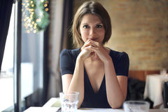 Young woman sitting at a restaurant table Royalty Free Stock Photography
