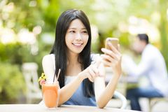 Young woman sitting in restaurant watching smart phone Stock Photos