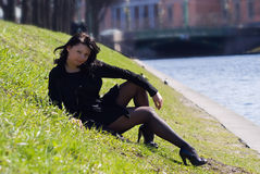Young woman sitting at the river channel Royalty Free Stock Photos