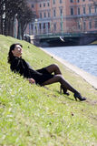 Young woman sitting at the river channel Stock Photography