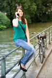 Young woman sitting by river and talking on phone Royalty Free Stock Photos