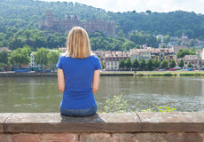 Young woman sitting on the riverside at Heidelberg Stock Image