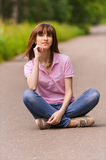 Young woman sitting on road Stock Photo