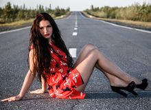 Young woman sitting on the road Stock Photo