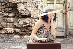 Young woman sitting on road with suitcase Stock Photos
