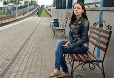 Young woman sitting on a roadside bench. Staring down the road towards the camera with a serious expectant expression as she waits for transport or a person to stock images