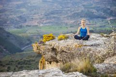 Young woman sitting on a rock in asana position Stock Photo