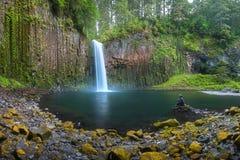 Young woman sitting on the rock at Beautiful waterfall of Abiqua Creek, Abiqua Falls, Oregon, USA. stock image