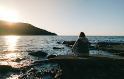 Young woman sitting on a rock, gazing in the distance, looking in the sea. stock photo