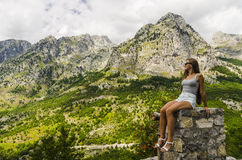 Young woman sitting on a rock and looking at beautiful mountains Royalty Free Stock Image