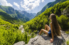 Young woman sitting on a rock and looking at beautiful mountains Stock Images