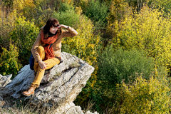 Young woman is sitting on the rock and watching to the autumn fo Stock Image