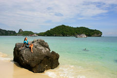 Young woman sitting on a rock at Wua Talab island, Ang Thong Nat Stock Photo