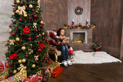 Young woman sitting on the rocking chair in the room Christmas t Stock Image