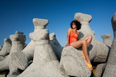 Young woman sitting on rocks Royalty Free Stock Photography