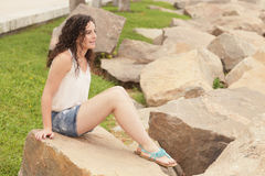 Young woman sitting on the rocks Stock Photography