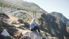 Young woman sitting on rocks below bridge Stock Images