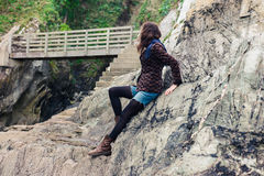 Young woman sitting on rocks Royalty Free Stock Photo