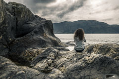 Young woman is sitting on the rocks near by fjord, Norway Royalty Free Stock Photos