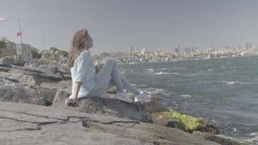 Beatiful young woman sitting on the rocks on sea coast in istanbul stock video footage
