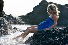 Young woman sitting on rocky beach in summer Royalty Free Stock Photo