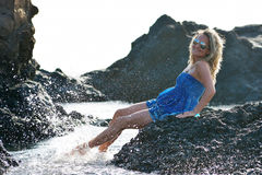 Young woman sitting on rocky beach in summer Stock Photos