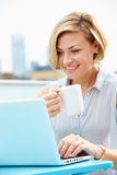 Young Woman Sitting On Roof Terrace Using Laptop Royalty Free Stock Photo