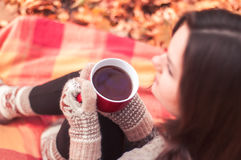 Young woman sitting on a rug and drinking tea Royalty Free Stock Photography