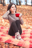 Young woman sitting on a rug and holding a big red cup Stock Photo