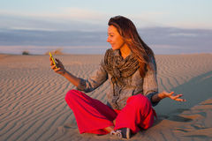 Young woman sitting on the sand in the desert and talking on Skype Stock Image