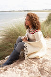 Young Woman Sitting In Sand Dunes. Wrapped In Blanket Stock Photography