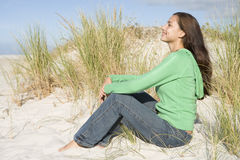 Young woman sitting in sand dunes Stock Photo